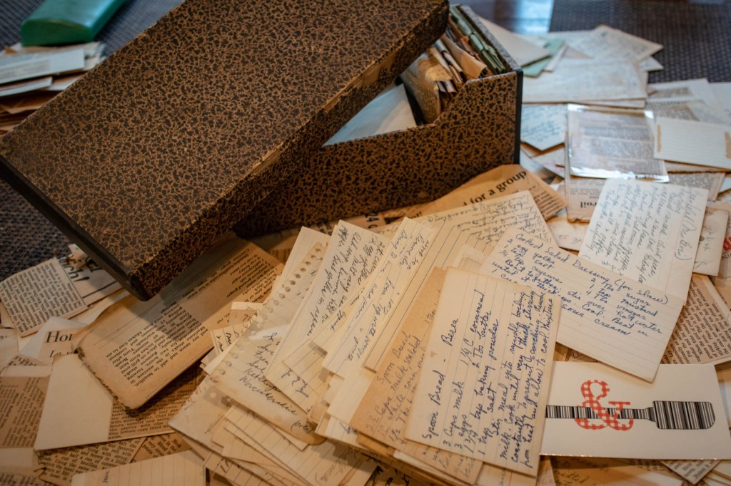 An old cardboard box surrounded by disorganized pile of handwritten recipe cards