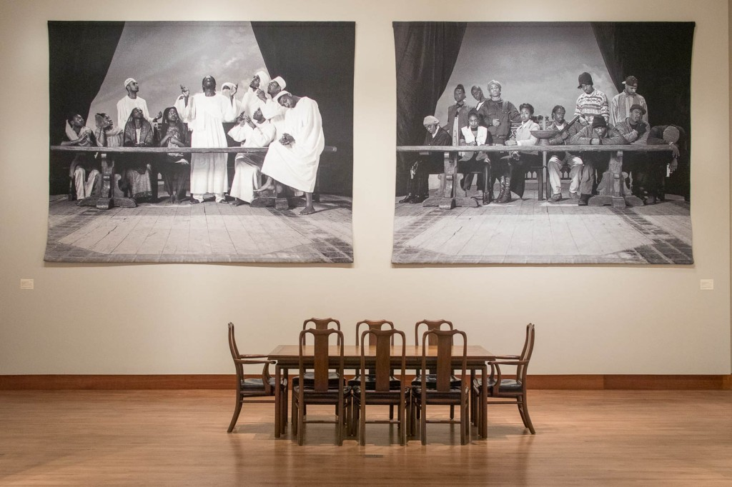 A dining table and 8 chairs below two very large photo tapestries.