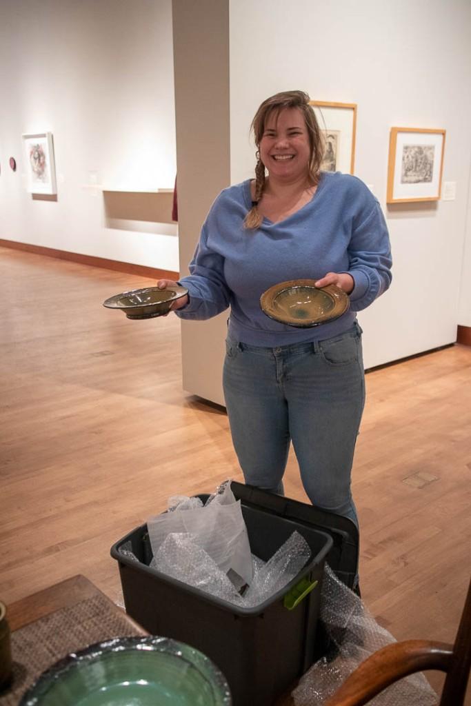 Hannah smiling as she unpacks ceramic bowls