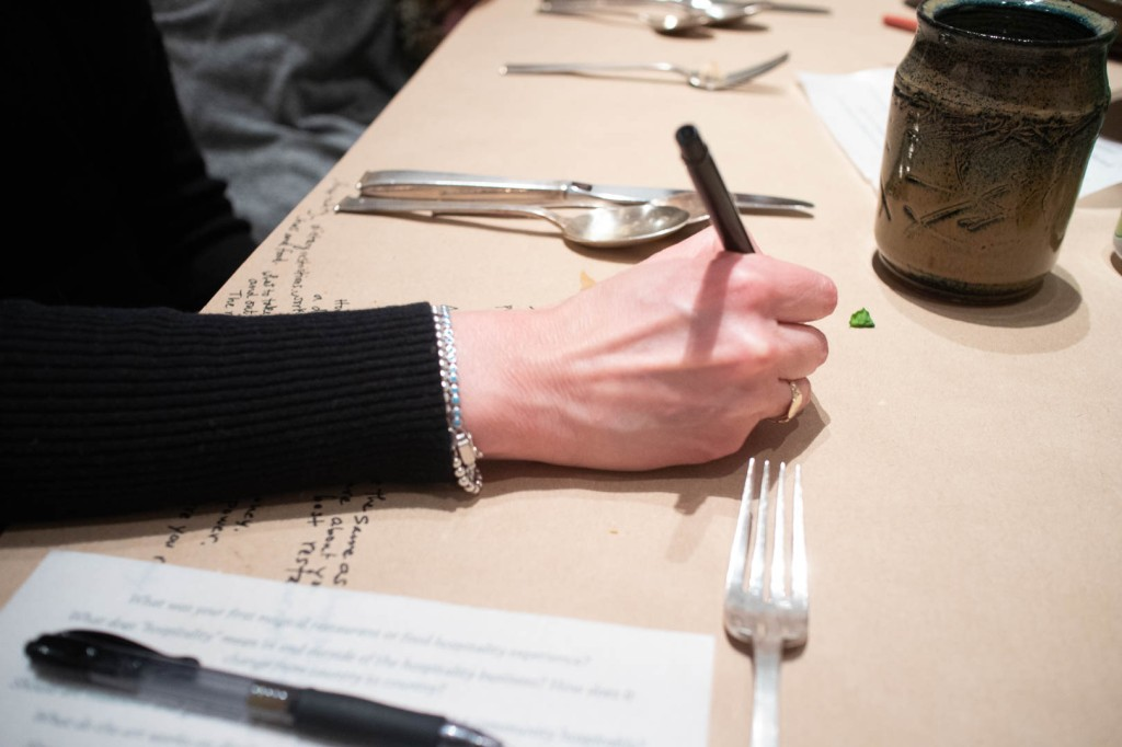 a guest's hand making notes on brown paper covering the table