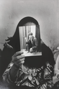a woman in a head covering holding a photograph of a young man in front of her face