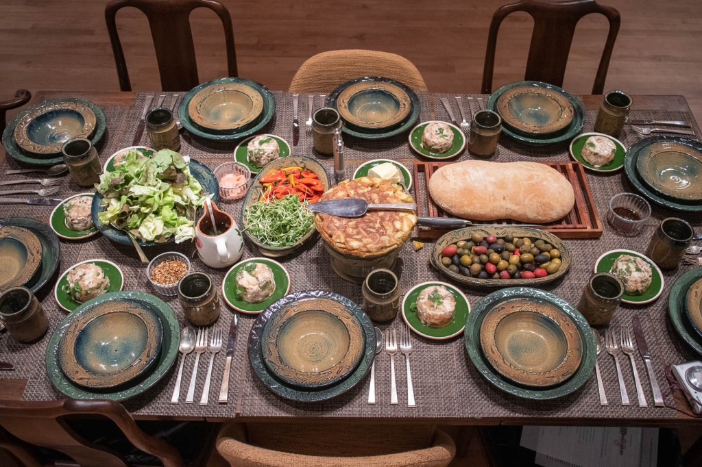 overhead view of table with handmade ceramics, bread, salad