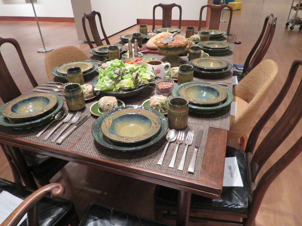 dining table with salad and bread and 8 place settings