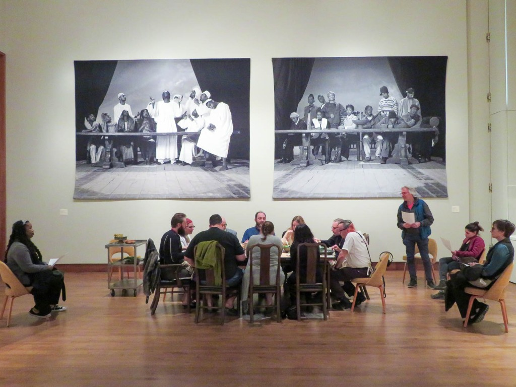 long view of 8 people at table with listeners sitting and standing around them
