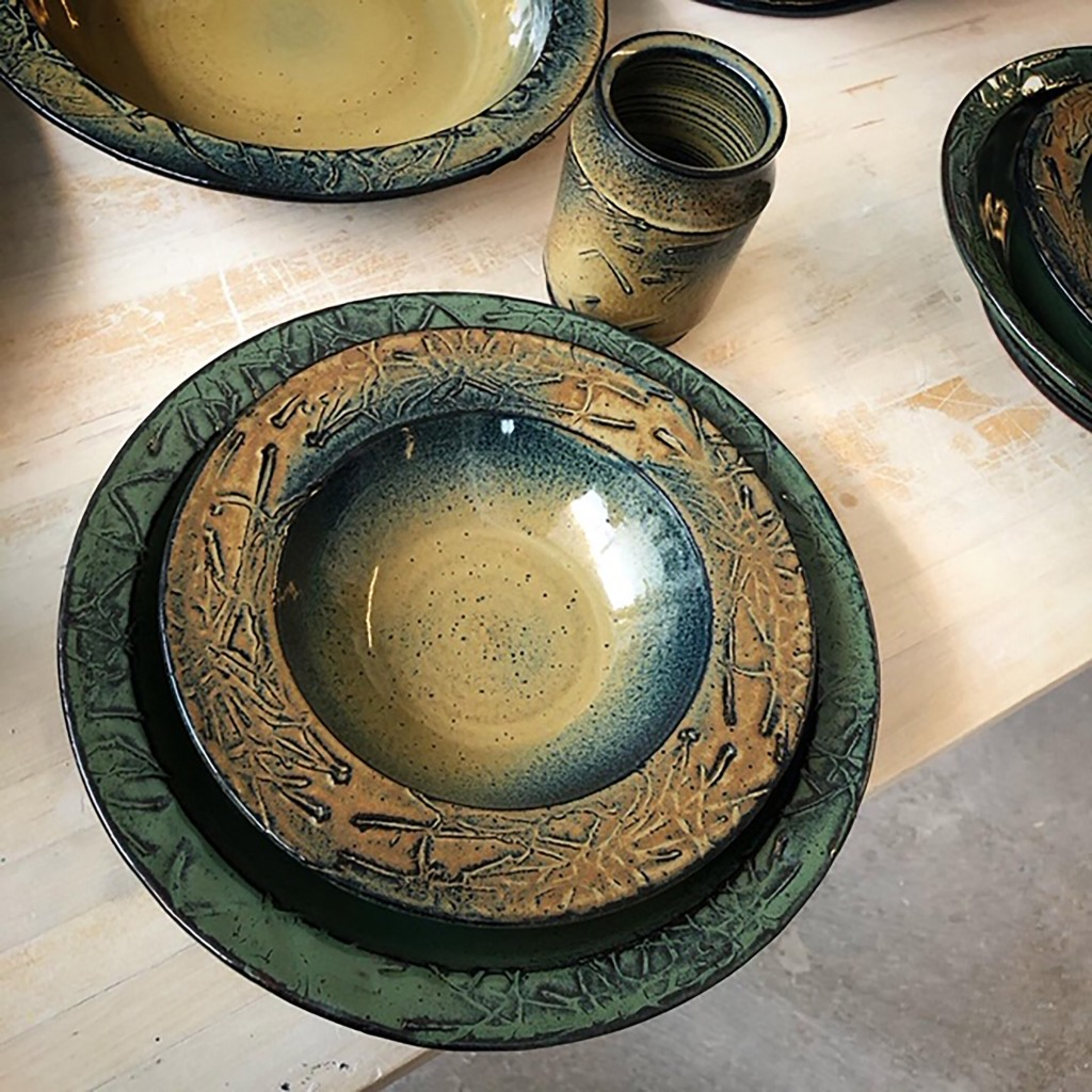 closeup of a place setting, including a large plate, shallow bowl, and drinking cup, in blue-green and brown ceramic