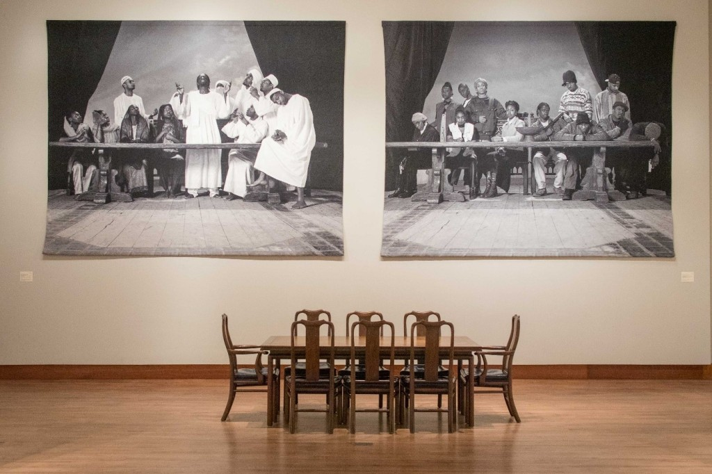 an empty dining table with 8 chairs below two large photo tapestries on the wall depicting black figures posed behind a table